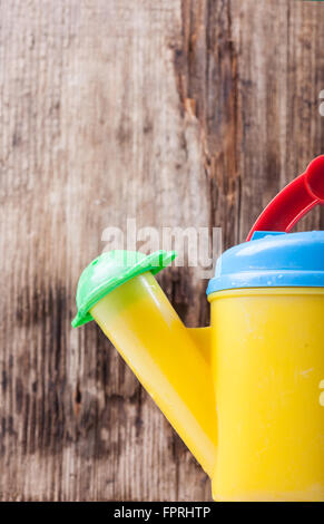Watering Can closeup on background of old wooden board - Stock Photo