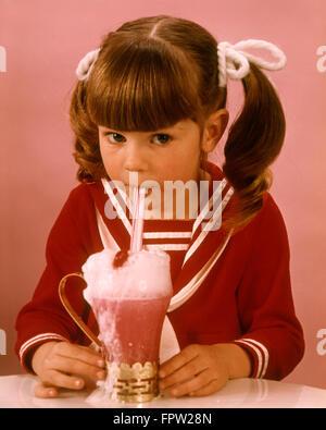 1960s 1970s BRUNETTE GIRL RED BLOUSE DRINKING PINK STRAWBERRY DRINK MILKSHAKE ICE CREAM SODA - Stock Photo