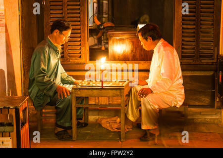 Men playing at the light of a candle a board game, Old Town of Hoi An, Vietnam - Stock Photo