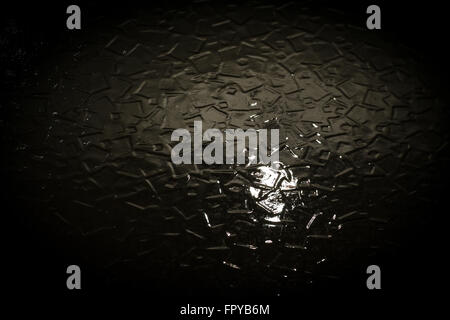 Home interior lightbulb shines through a dark glass window creating fractured light against a black backdrop. Abstract - Stock Photo
