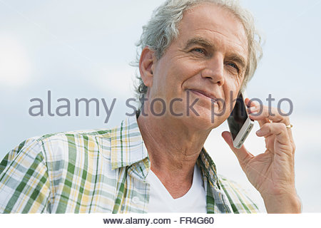 Senior man listening on cell phone outdoors. - Stock Photo