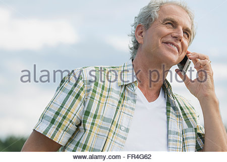 Senior man smiling while on cell phone conversation. - Stock Photo