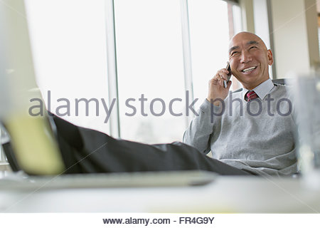 Mature Asian businessman with feet up on desk. - Stock Photo