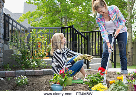 mature mother and daughter working on flower garden - Stock Photo