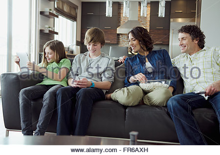 family on couch engaged with technology - Stock Photo