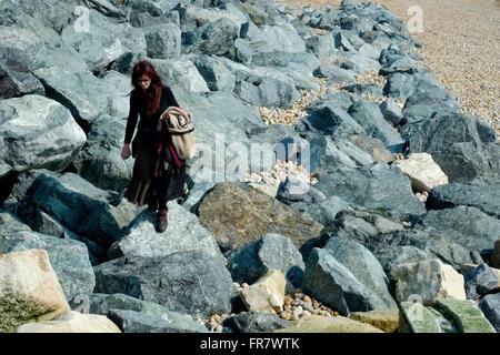 lone female walking over large rocks southsea beach england uk - Stockfoto