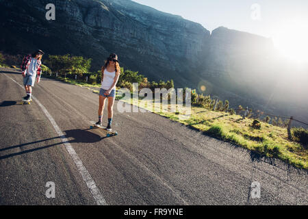 Two young people skating outdoors on rural road. Man and woman longboarding on a summer day. - Stock Photo