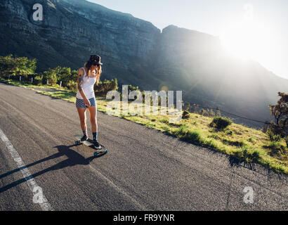 Young woman skating outdoors on rural road. Female longboarding on a summer day. - Stock Photo