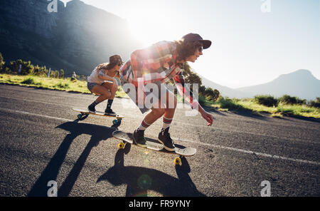 Side portrait of young people skateboarding together on road. Young man and woman longboarding down the road on - Stock Photo