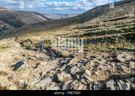 Male mountain biker pushing his bike up Jacob's Ladder towards Kinder Scout in the Peak District, Derbyshire, England, - Stock Photo