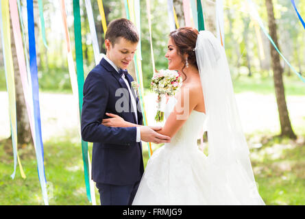 Bride and groom at wedding Day walking Outdoors on spring nature. - Stock Photo