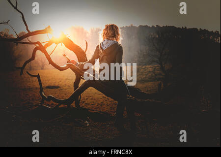 young woman siting on a fallen tree in sunset park - Stock Photo
