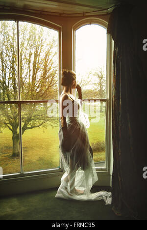young female standing by the window - Stock Photo