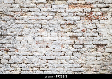 Old red brick wall with white paint layer, close up background photo texture - Stock Photo