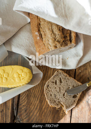 Top view, rustic bread wrapped in a linen cloth and butter on a wooden table, slice of bread and knife - Stock Photo