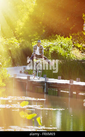 A good looking man with a hat is having fun ridding a bike with his legs up on a wodden pontoon at the park. He - Stock Photo