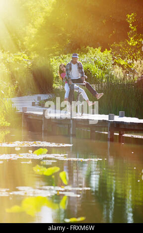 A smiling couple is having fun riding the same bike on the wooden pontoon of a lake. They are enjoying a sunny day - Stock Photo