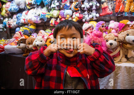 Young boy pulling a grimace, funny face at Temple Street Night Market, Tsim Sha Tsui, Kowloon, Hong Kong - Stock Photo