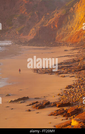 The beautiful sunset at Portugal coast in autumn.Alone woman walking on a beach. Loneliness concept. - Stock Photo