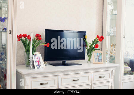 light room with white furniture and tulips - Stockfoto