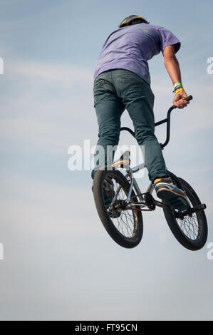 Biker in mid-air performing dirt jumping on bright,sunny day - Stock Photo