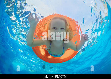 Funny underwater photo of baby girl swimming with fun on orange tube and diving in clear aqua park pool. - Stock Photo