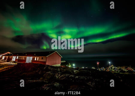 Green bright Northern lights above the clouds, over the fjord and arctic capital Nuuk city, Greenland, October 2015 - Stock Photo