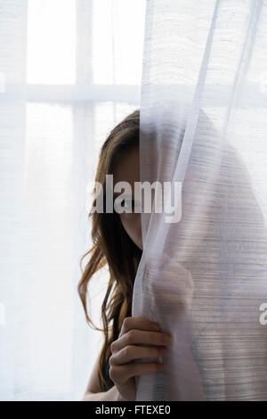 Serious young woman hiding behind the curtains by the window - Stock Photo