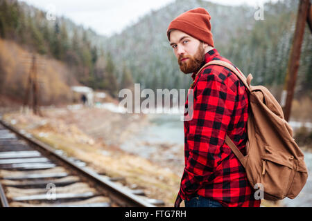 Handsome bearded young man in checkered shirt on railway road in mountains - Stock Photo