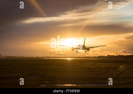 A British Airways Boeing 777-300 lands at London Heathrow as the sunset illuminates the clouds. - Stock Photo