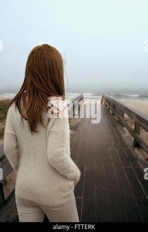 Woman walking on wooden boardwalk at beach - Stock Photo