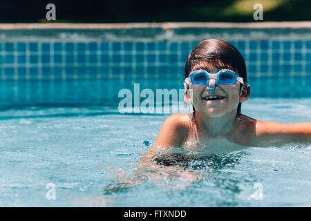 Smiling boy wearing goggles and nose clip in swimming pool - Stock Photo