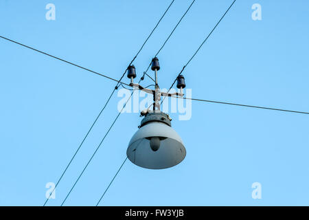 Old street lamp hanging on wires on blue sky - Stock Photo