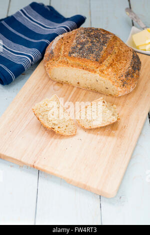 Loaf of freshly baked sliced homemade Struan bread, on a rustic blue table. - Stock Photo