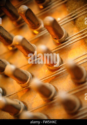 Piano mechanism - close-up of bushed tuning pins in pin block , wrest plank, and triple piano strings, of Bechstein - Stock Photo