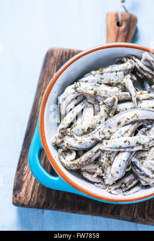 Anchovy with herbs in traditional tapas ceramic bowl, from overhead on wooden board - Stock Photo