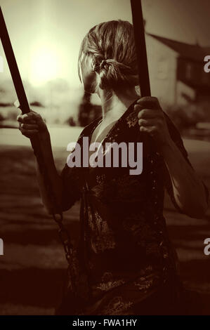 young woman sitting on the swing - Stock Photo