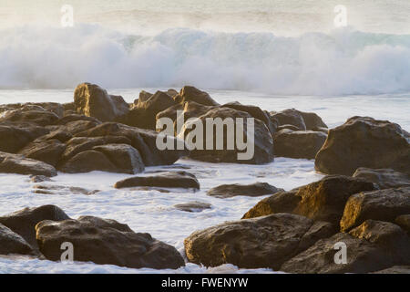 White frothy water rushes in dangerously over some rocks on the north shore of Oahu during a huge storm in the ocean. - Stock Photo