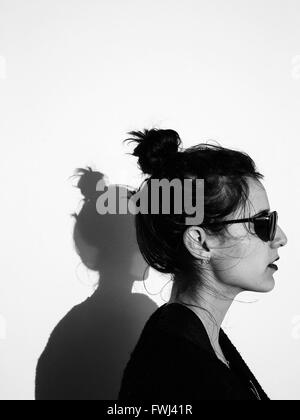 Profile View Of Woman Wearing Sunglasses Against Wall - Stock Photo