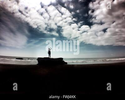 Silhouette Of Woman Dancing On Beach Against Cloudy Sky - Stock Photo