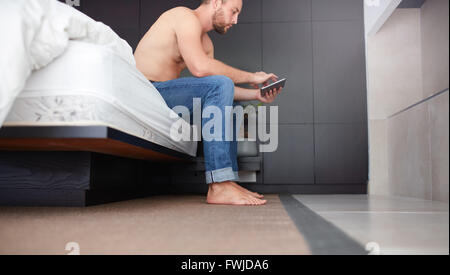 Side portrait of a young man sitting on bed in bedroom and using digital tablet. - Stock Photo