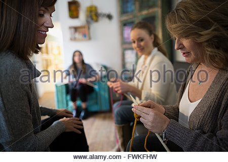 Women learning knitting at yarn store - Stock Photo