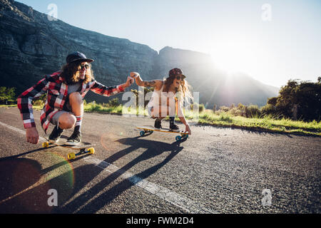 Happy young couple having fun with skateboard on the road. Young man and woman skating together on a sunny day. - Stock Photo