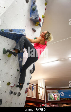Young teen girl climbs up an artificial climbing wall - Stockfoto