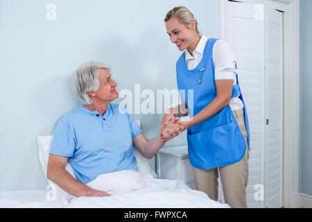 Nurse holding senior man hand in hospital - Stock Photo