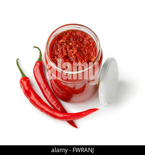Glass jar with traditional Indonesian Sambal and fresh red chili peppers on white background - Stock Photo