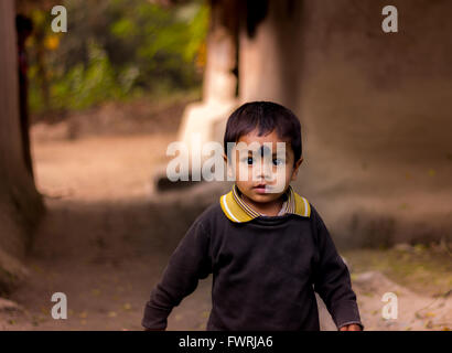 An Indian village kid running and smiling in the rainforests of Sundarban, West Bengal, Kolkata - Stock Photo