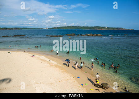 Locals people at beach below lighthouse at Old Town of Galle, Sri Lanka, Asia - Stock Photo