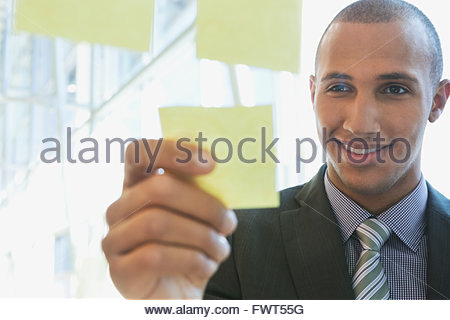 Young businessman putting sticky note on glass - Stockfoto