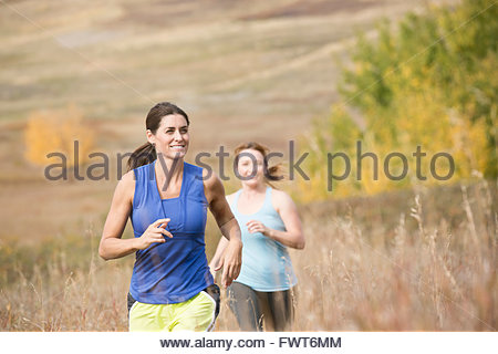 Two women running outdoors together. - Stock Photo